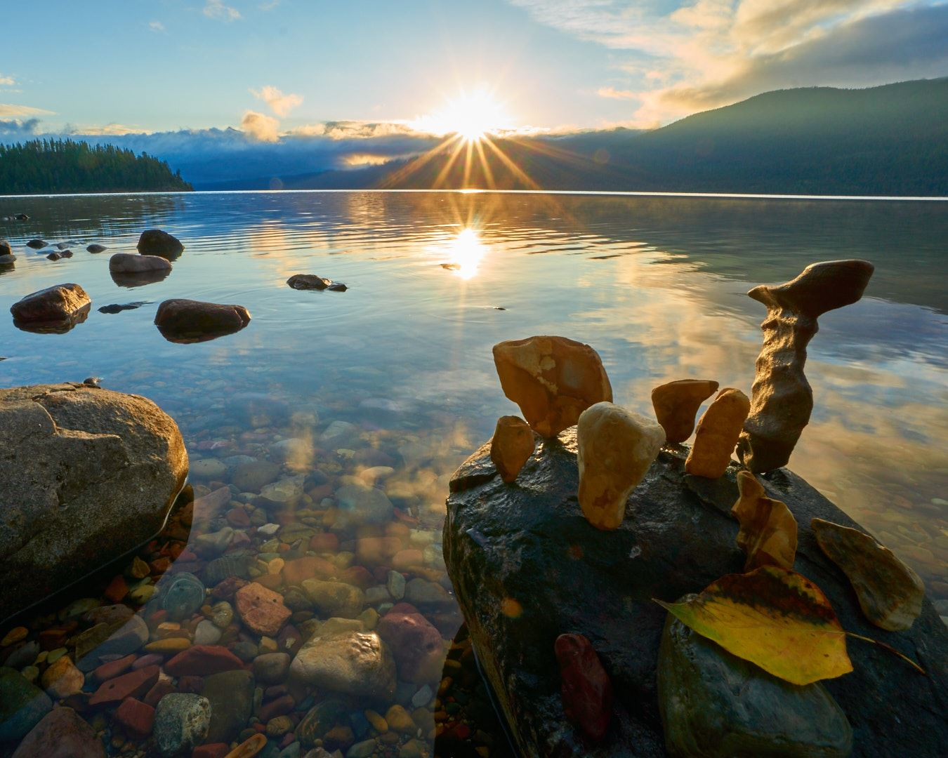 Sunrise over lake with rocks and mountains in background