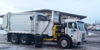 Solid Waste Truck Picking Up Can in Winter